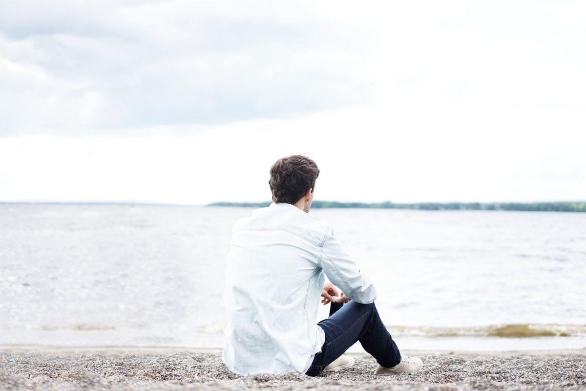 1人で海を見る男性