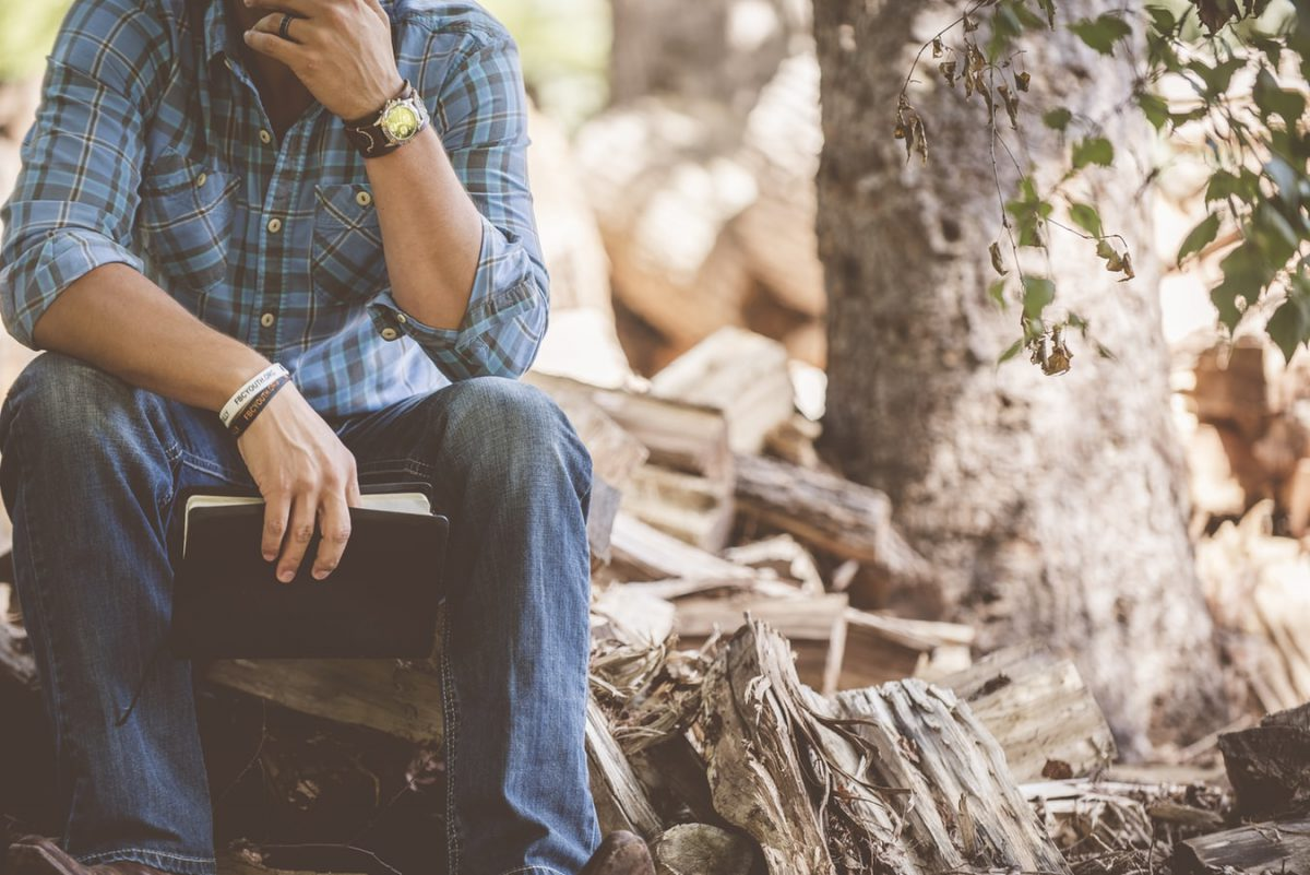 木の隣で座る男性