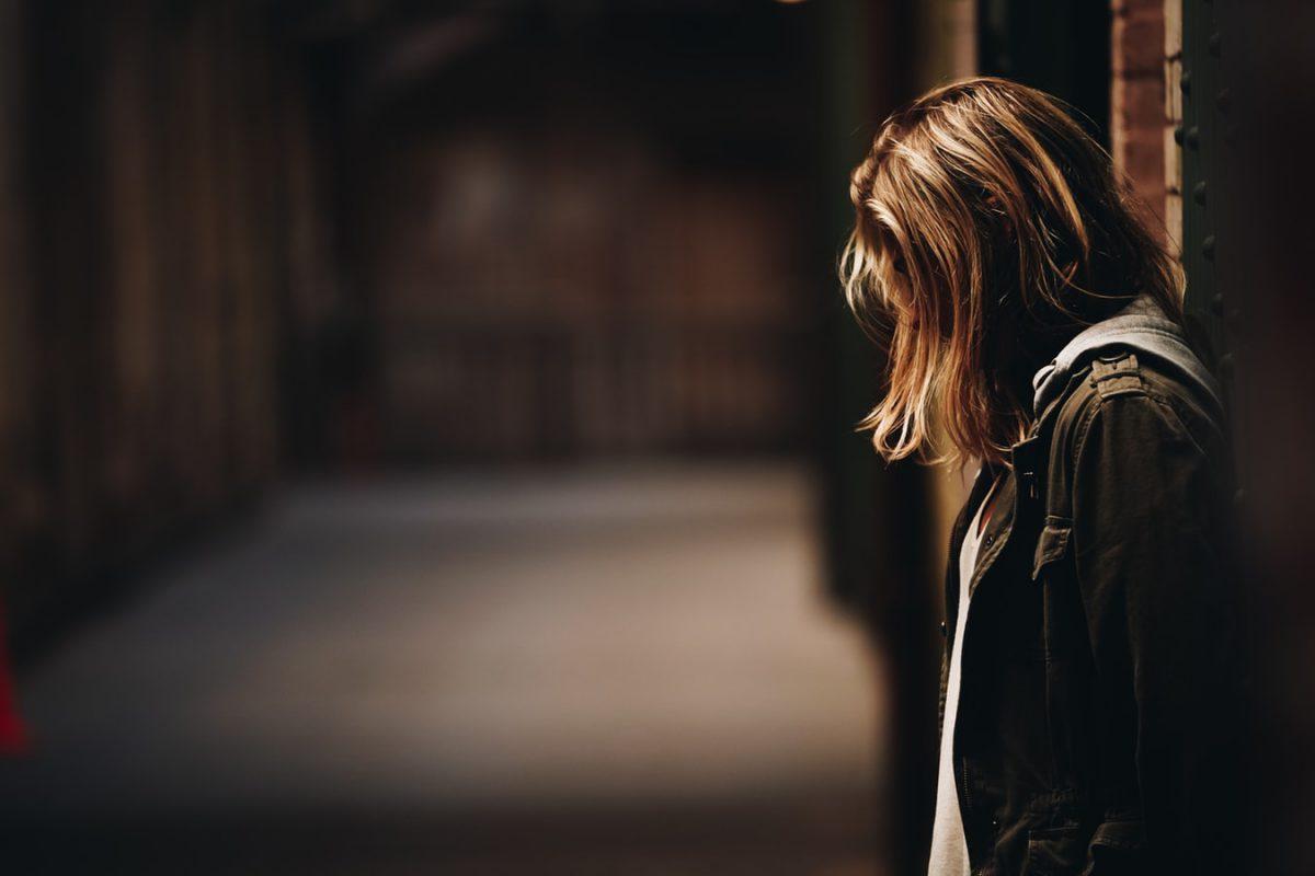 壁に寄り掛かる悲しげな女性